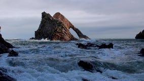 Vagues orageuses rugueuses se brisant contre une pile de roche de mer en Ecosse pendant un après-midi orageux d'automne banque de vidéos