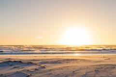 Vagues rugueuses au coucher du soleil sur une plage sablonneuse avec des réflexions sur W Photos stock
