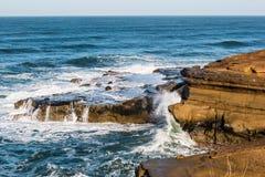 Vagues se brisant au-dessus des formations de roche aux falaises de coucher du soleil images stock