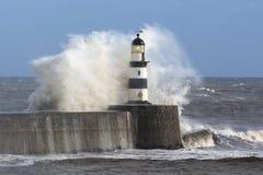 Vagues se brisant au-dessus du phare de Seaham Photos stock