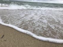 Vagues se brisant dans le sable Image libre de droits