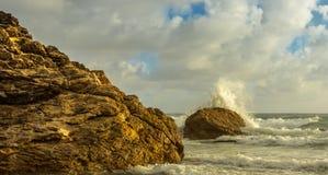 Vagues se brisant sur des roches au lever de soleil Image stock