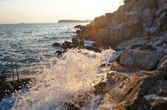 Vagues se brisant sur les roches au coucher du soleil Images libres de droits