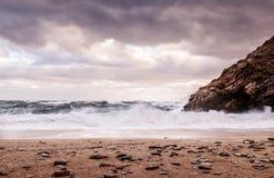 Vagues se brisant sur une plage abandonnée et dramatique avec les nuages déprimés foncés dans le ciel Photos stock