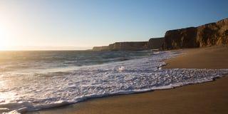 Vagues sur une plage avec de hautes falaises au coucher du soleil Photo stock
