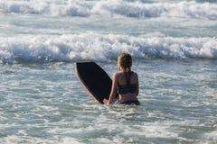 Vagues surfantes de natation de fille photographie stock