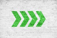 Vai adiante o sentido apontando dos sinais da seta direcional do verde pintado em um fundo cinzento branco da textura do quadro i foto de stock royalty free