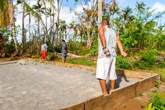 Vailala, Wallis and Futuna. Indigenous aboriginal Polynesian people are playing petanque. Uvea. Men are wearing skirts lava-lava. royalty free stock photography