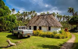Vailala, Wallis and Futuna. A typical rural cottage in Wallis resembles traditional thatched roof Polynesian fale. Pickup car. stock images