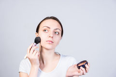 Vain Girl Applying Foundation Makeup on her Face Royalty Free Stock Image