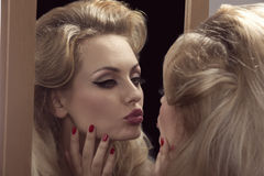 Vain girl in front of the mirror. Close-up portrait of elegant blonde girl looking her cute make-up in to the mirror, posing with classic hair-style and red nail Stock Images