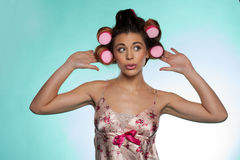Vain pretty young woman showing her hair rollers. Portrait of a vain pretty young woman wearing a flowery satin summer pajama showing her hair rollers Stock Photos