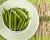 Vainas de habas verdes en Placemat de bambú Fotos de archivo libres de regalías