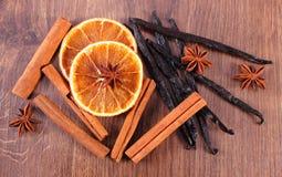 Vainilla fragante, canela, anís de estrella y naranja secada en superficie de madera Imagen de archivo