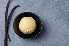 Vainilla hecha en casa, helado del caramelo en cuenco negro con las vainas de la vainilla Espacio orgánico de la copia de la opin Fotografía de archivo