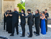 VAISON LA ROMAINE, FRANCE - AUGUST 4, 2016: Choral singers make a massage of each other before the performance. Relaxation royalty free stock images