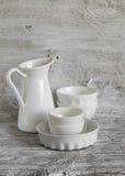 Vaisselle blanche de vintage - cruche émaux, cuvette en céramique et plat de cuisson Photo libre de droits