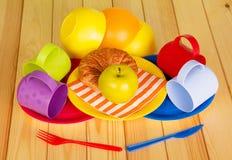 Vaisselle colorée, croissant et une pomme sur le fond du bois léger Photographie stock libre de droits