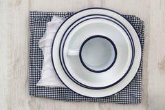 Vaisselle d'ustensiles en émail de vintage sur de rétros tissus sur le CCB en bois rustique Photos stock