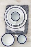 Vaisselle d'ustensiles en émail de vintage sur de rétros tissus sur le CCB en bois rustique Images libres de droits