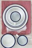 Vaisselle d'ustensiles en émail de vintage sur de rétros tissus sur le CCB en bois rustique Images stock