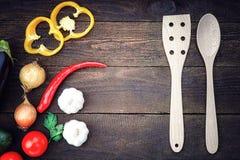 Vaisselle de cuisine en bois avec des légumes sur la table Image stock
