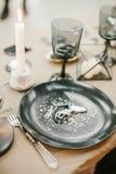 Vaisselle de mariage avec la carte nominative, chandelier en pierre avec la bougie, fourchette argentée Photographie stock libre de droits