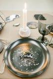 Vaisselle de mariage avec la carte nominative, chandelier en pierre avec la bougie, fourchette argentée Photographie stock
