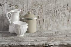 Vaisselle de vintage - émaillez la cruche, le pot émaux et la cuvette en céramique blanche sur la surface en bois lumineuse Image libre de droits