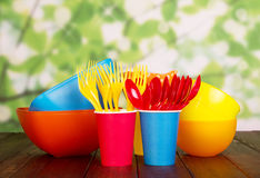 Vaisselle en plastique colorée : cuvettes, fourchettes, cuillères sur le vert abstrait Photographie stock