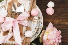 Vaisselle et argenterie avec des décorations Pivoines et meringues rose-clair sur le fond en bois photos libres de droits