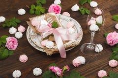 Vaisselle et argenterie avec les roses rose-clair gonflées Image stock