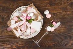 Vaisselle et argenterie avec les roses rose-clair gonflées sur le fond en bois Image libre de droits