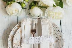 Vaisselle et argenterie avec un bouquet des pivoines blanches sur les vieux conseils en bois blancs photos stock