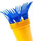 Vaisselle, tasses et fourchettes en plastique lumineuses sur le fond blanc, Se Image libre de droits