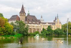 Vajdahunyad Castle - Budapest. Paddlers among pieces of modern art exhibited on the artificial lake that surrounds Vajdahunyad Castle in the City Park - Budapest stock photo