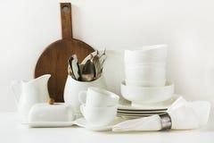 Vajilla blanco para servir La loza, el plato, los utensilios y otra diversa materia blanca en tablero blanco Todavía de la cocina foto de archivo libre de regalías