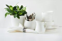 Vajilla blanco para servir La loza, el plato, los utensilios y otra diversa materia blanca en tablero blanco Todavía de la cocina imagenes de archivo