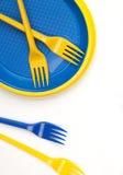 Vajilla disponible plástico azul y amarillo brillante en el CCB blanco Fotos de archivo libres de regalías