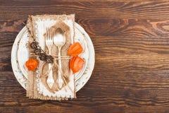 Vajilla con el Physalis y los cubiertos anaranjados Foto de archivo