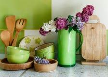 Vajilla de cerámica y de madera de la cocina, ramo de lila en la jarra plástica verde Foto de archivo libre de regalías