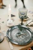 Vajilla de la boda con la tarjeta de presentación, palmatoria de piedra con la vela, bifurcación de plata Fotografía de archivo