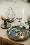 Vajilla de la boda con la tarjeta de presentación, palmatoria de piedra con la vela, bifurcación de plata Fotos de archivo libres de regalías