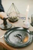 Vajilla de la boda con la tarjeta de presentación, palmatoria de piedra con la vela, bifurcación de plata Fotos de archivo
