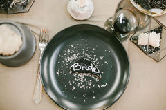 Vajilla de la boda con la tarjeta de presentación, palmatoria de piedra con la vela, bifurcación de plata Imágenes de archivo libres de regalías