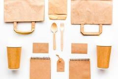 Vajilla disponible La taza de papel, cuchara, bifurca cerca de mofa de la bolsa de papel marrón, de la etiqueta y de la opinión s fotos de archivo