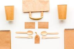 Vajilla disponible La taza de papel, cuchara, bifurca cerca de mofa de la bolsa de papel marrón, de la etiqueta y de la opinión s imagen de archivo