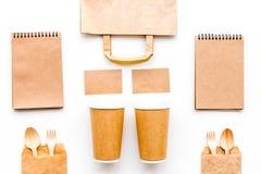 Vajilla disponible La taza de papel, cuchara, bifurca cerca de mofa de la bolsa de papel marrón y de la opinión superior del cuad fotografía de archivo