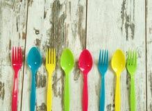 Vajilla plástico colorido en tableros Imagen de archivo