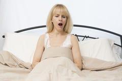 Vak övre Tid:  Den mellersta ålderkvinnan gäspar i säng Royaltyfria Bilder
